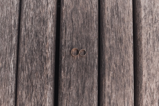 Wedding rings bride and groom on wooden background