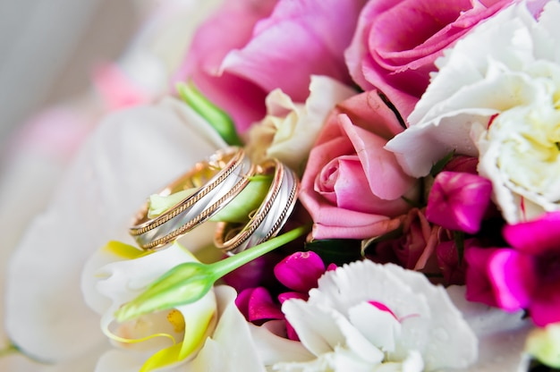 Wedding rings on the bride's bouquet of roses and koalas.