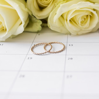 Wedding rings on calendar date with yellow roses