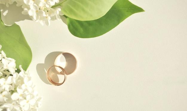 Обручальные кольца крупным планом на фоне белых нежных романтических цветов