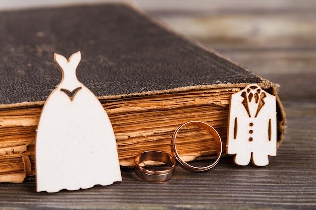 Костюмы обручальных колец и старая книга. библия крупным планом и золотые кольца.