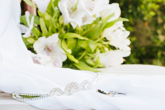 Wedding rings; crown; scarf near the flower bouquet on table