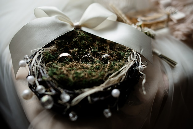 Wedding rings on the decorated nest with greenery and white ribbon