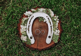Wedding rings decorated on a wooden cut with white flowers on the grass