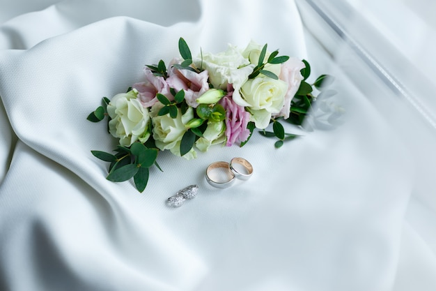 Wedding rings and earrings lying near gentle hairpin with flowers