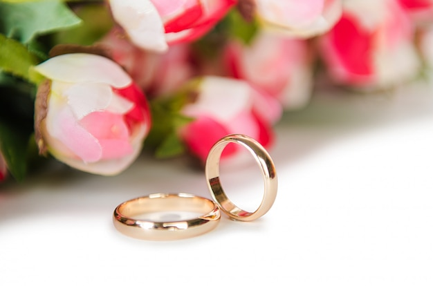 Wedding rings and flowers isolated on white background