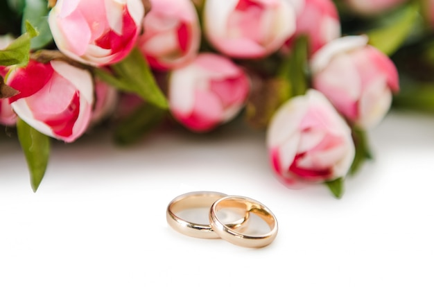 Wedding rings and flowers isolated on white
