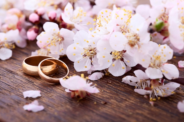 Wedding rings and flowers on wooden desk.