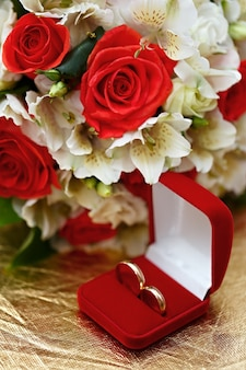 Обручальные кольца, подарочная коробка и цветы для невесты.