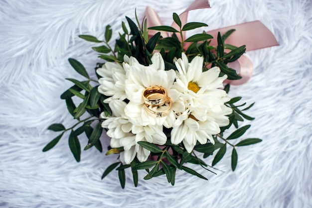 Wedding rings, gold and diamond on a white chrysanthemum, close-up. two beautiful rings on the wedding bouquet, top view.