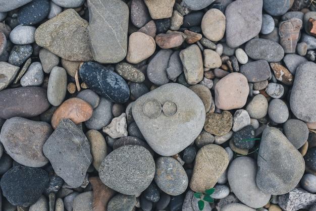 Wedding rings on gray stones
