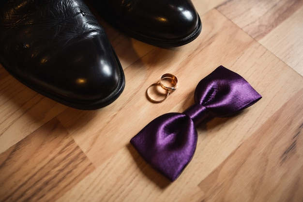 Wedding rings, groom's shoes and purple bow tie on wooden floor