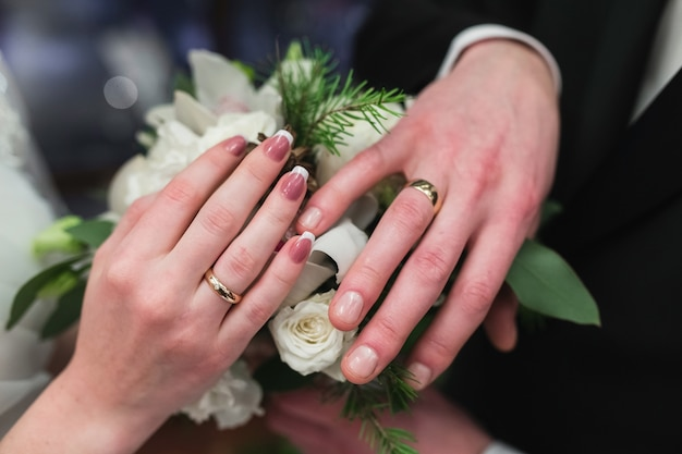 Wedding rings on the hands of the newlyweds.