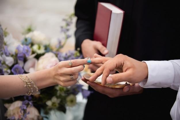結婚指輪。新しい幸せな家族の創造を象徴するリングを交換する厳粛なプロセスでの新郎新婦の手。花嫁が結婚式中に新郎の指に指輪を置く