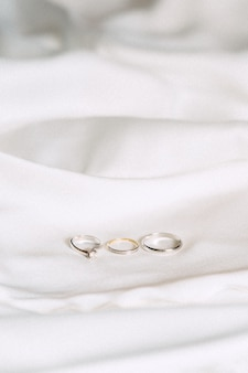 Обручальные кольца высокого угла зрения на ткани на белом фоне