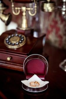 Обручальные кольца в коробке на фоне старого телефона