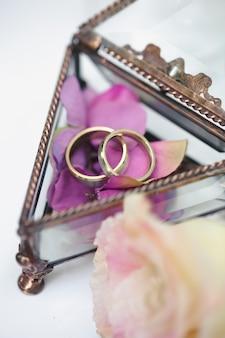 Обручальные кольца в стеклянной шкатулке с лепестками сиреневых роз
