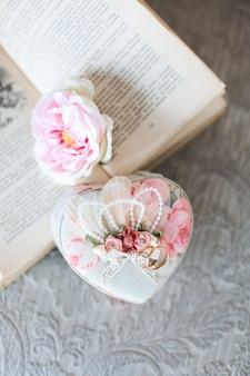 ヴィンテージの本の上に横たわる美しい装飾的な棺の結婚指輪
