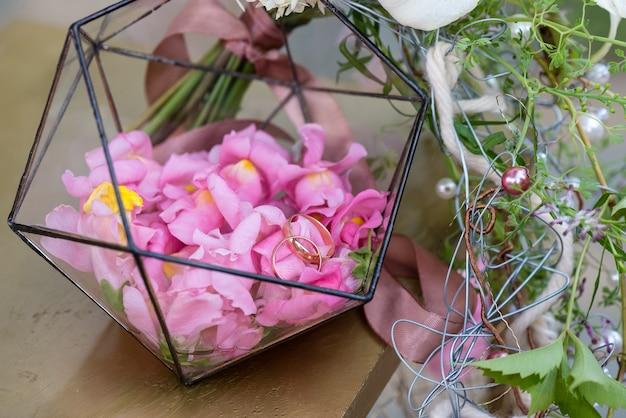 장미 꽃잎이 있는 부토니에 결혼 반지