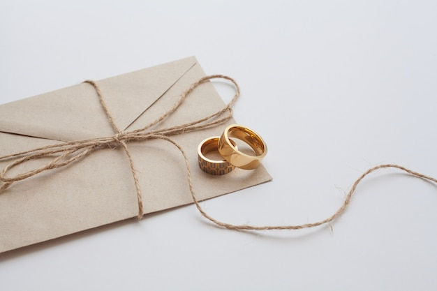 Wedding rings on invitation card with brown thread