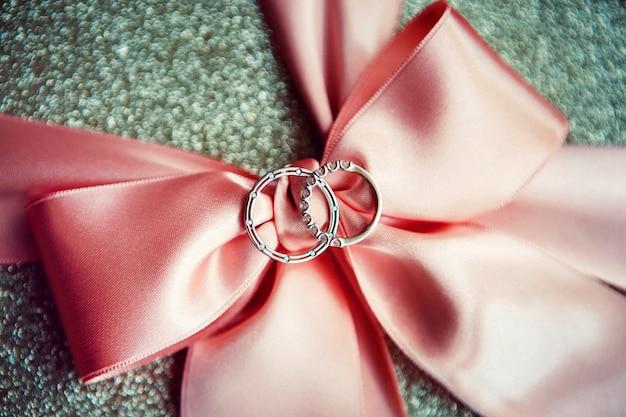 結婚指輪。ホワイトとイエローゴールドのジュエリー。サテンリボンの結婚指輪。白いレース。