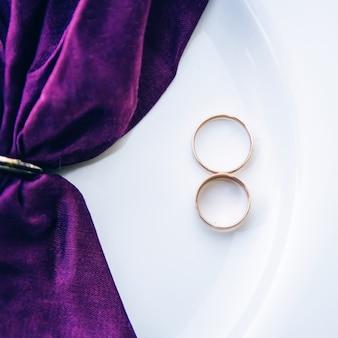 結婚指輪。ジュエリーホワイトとイエローゴールド。白い背景の上の結婚指輪。