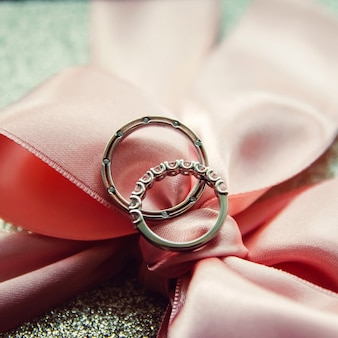 Wedding rings. jewelry in white and yellow gold. wedding ring on satin ribbon. white lace.