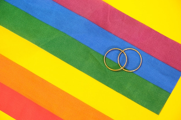 Wedding rings on lgbt flag, yellow background, copy space. top view