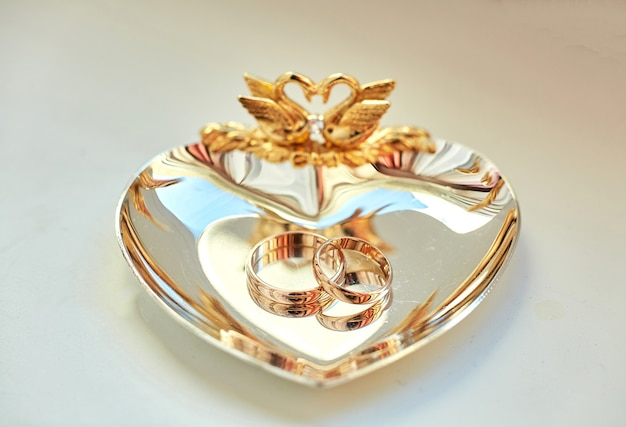 Wedding rings lie on the beautiful golden plate decorated