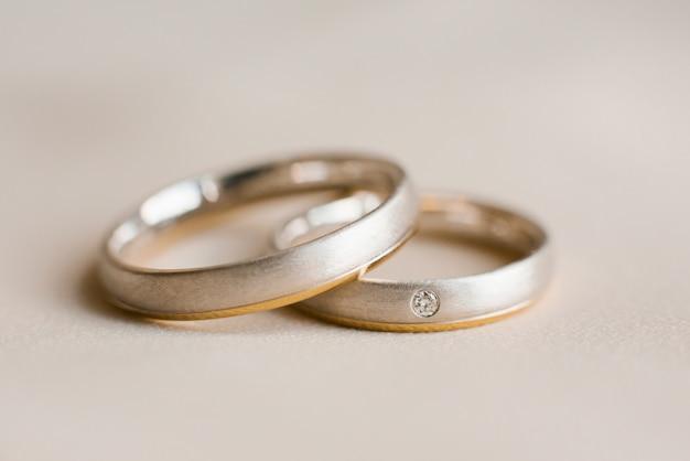 Wedding rings lie on beige