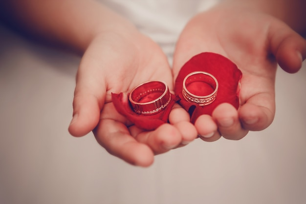Wedding rings lie on children's palms with petals of roses
