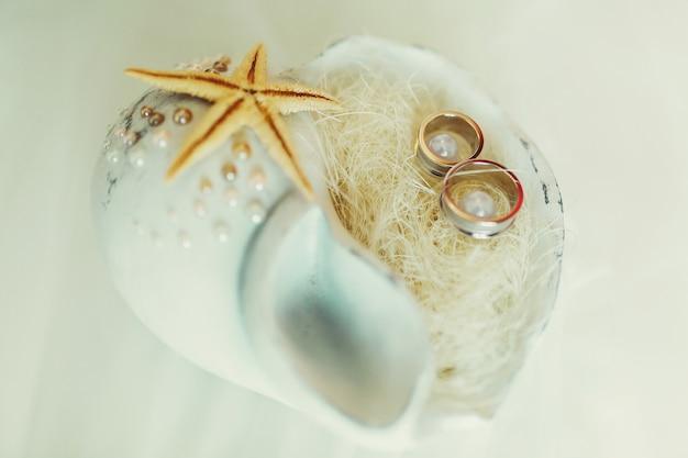 Обручальные кольца лежат в белой раковине с небольшим жемчугом