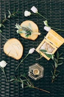 Обручальные кольца лежат в деревянном ящике в окружении цветов и веток с листьями на плетеной зелени.
