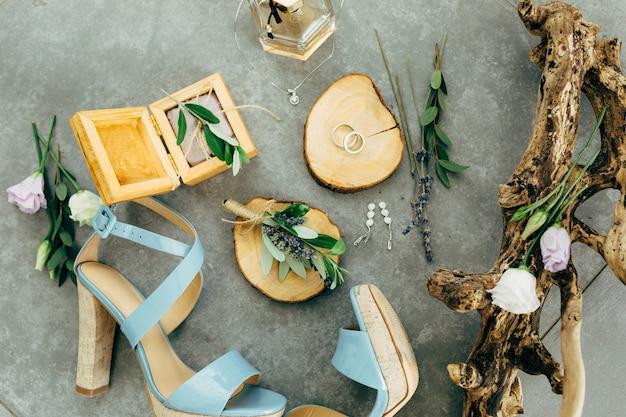 Обручальные кольца лежат на деревянной подставке в окружении босоножек на каблуках в деревянной коробке парфюмерных цветов.