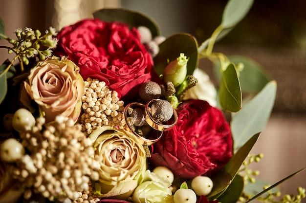Обручальные кольца лежат на красивом букете как аксессуары невесты.