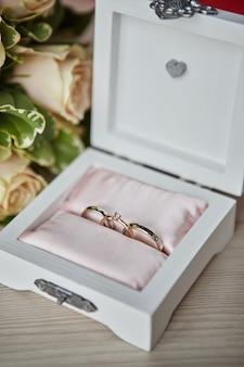 Обручальные кольца лежат на красивой коробке с цветами в качестве свадебных аксессуаров.