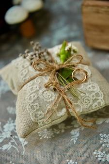결혼 반지는 아름답고 장식적인 손으로 만든 베개에 놓여 있습니다.