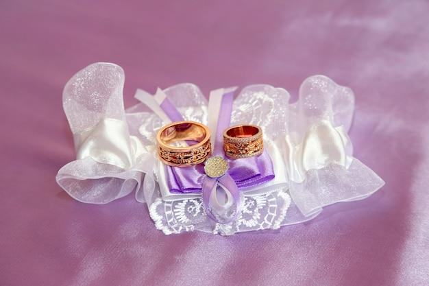 아름답게 장식 된 천에 결혼 반지가 놓여 있습니다.