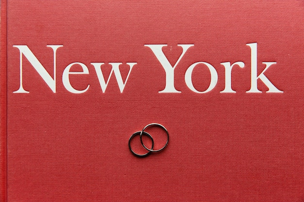 Обручальные кольца лежат на красной книжке с надписью «нью-йорк»