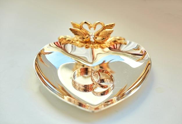 Обручальные кольца лежат на красивой золотой тарелке, украшенной