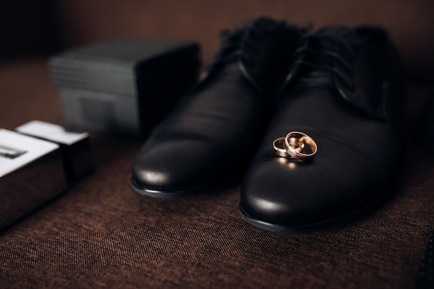 Обручальные кольца лежат на мужской обуви