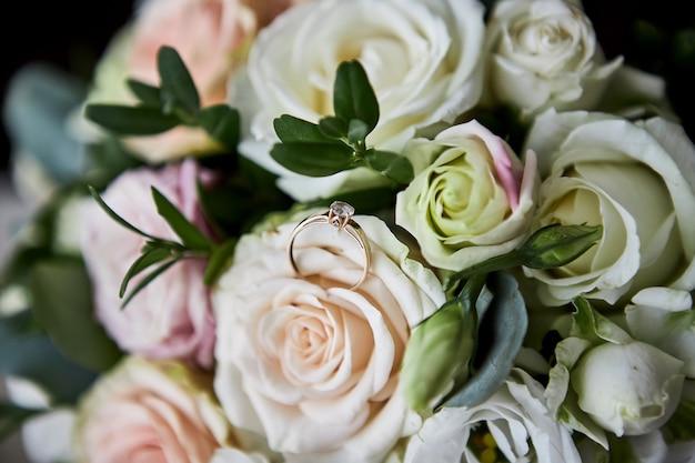 Обручальные кольца лежат на свадебном букете