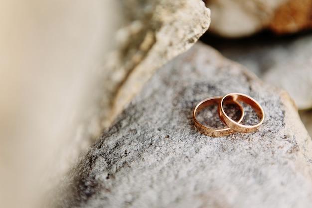 Wedding rings lie on the rock.