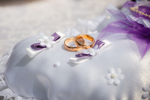 Wedding rings lie on a small pillow