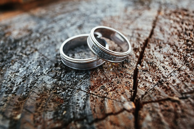 Wedding rings lie on a wooden block