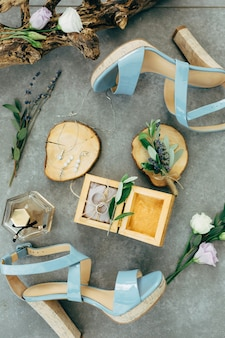 Wedding rings lie in a wooden box surrounded by sandals with heels flowers and twigs on the floor