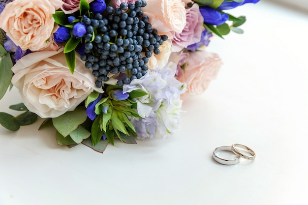 Wedding rings lie on wooden surface against background of bouquet of flowers