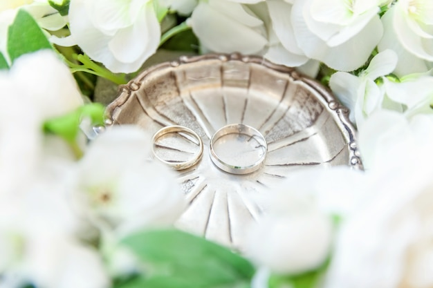 Wedding rings lie on wooden surface of bouquet of flowers