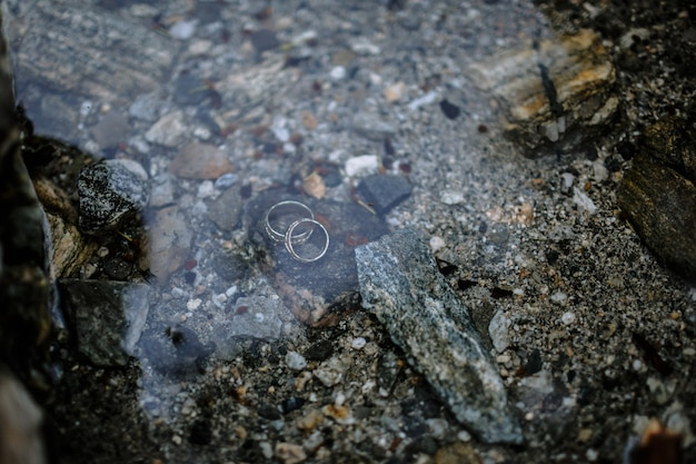 Обручальные кольца, лежащие под водой на дне озера
