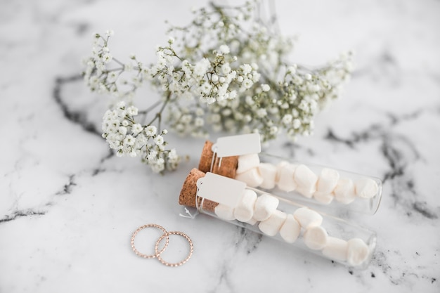 Wedding rings; marshmallow test tubes with tag and baby's-breath flowers on white textured background